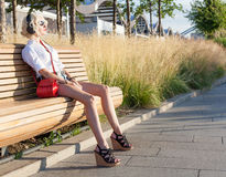 Fashion leggy girl in a beautiful high-heeled shoes in short denim shorts in the summer sitting on the bench in the headphones at Royalty Free Stock Photo