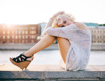Free Fashion Leggy Girl In A Beautiful High-heeled Shoes Sitting On The Waterfront At Summer Sunset Stock Photos - 57863623