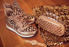 Fashion Leopard sneakers with Glamour golden wristwatch and purse on wooden background. Stock Images