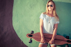 Fashion lifestyle, Beautiful young blonde woman with skateboard. Standing near the wall with graffiti at the day time Royalty Free Stock Photos