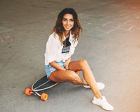 Fashion lifestyle, beautiful young woman with longboard. Lightle Stock Photography