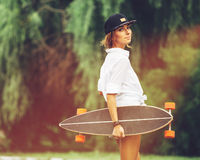 Fashion lifestyle, beautiful young woman with longboard. Lightleak effect and instagram filter Stock Photo
