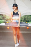 Fashion lifestyle, beautiful young woman with longboard Royalty Free Stock Images