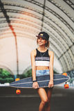 Fashion lifestyle, beautiful young woman with longboard Stock Photos