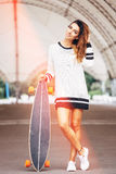 Fashion lifestyle, beautiful young woman with longboard Royalty Free Stock Photo