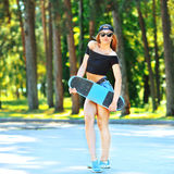 Fashion lifestyle. Beautiful young woman with skateboard - full Stock Photo