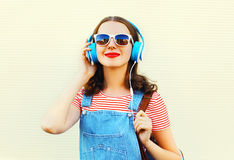 Fashion lifestyle portrait of happy woman is listens to music in headphones over white stock image