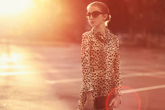 Fashion lifestyle portrait woman in a dress with leopard print. Evening sunny ghetto, street fashion photo stock photo
