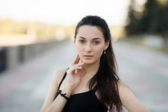 Fashion lifestyle portrait young brunette pretty woman posing in the city quay summer sunset evening showing street fashion ideas Royalty Free Stock Photography