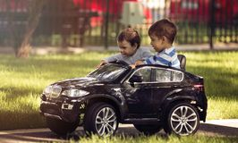 Little boy and girl driving toy car in a park. Fashion little boy driving electric toy car on alley of the park in Bucharest. Little girl next to boy trying to stock photos
