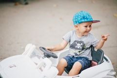 Fashion little boy driving toy car in a park Stock Photography