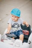 Fashion little boy driving toy car in a park Royalty Free Stock Photography