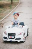 Fashion little boy driving toy car in a park Royalty Free Stock Photos