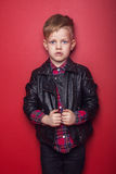 Fashion little boy wearing a leather jacket. Studio portrait over red background Stock Photos