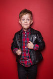 Fashion little boy wearing a leather jacket. Studio portrait over red background Royalty Free Stock Photography