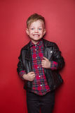 Fashion little boy wearing a leather jacket. Studio portrait over red background Stock Photo
