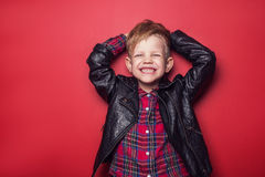 Fashion little boy wearing a leather jacket. Studio portrait over red background Stock Images