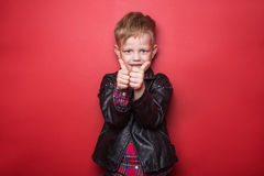 Fashion little boy wearing a leather jacket. Studio portrait over red background Royalty Free Stock Photo