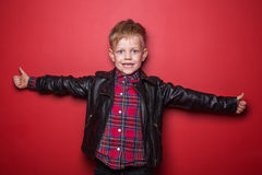 Fashion little boy wearing a leather jacket. Studio portrait over red background Royalty Free Stock Photos