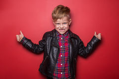 Fashion little boy wearing a leather jacket. Studio portrait over red background Royalty Free Stock Images