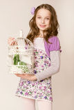 Fashion little girl with birdcage Stock Photos