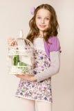 Fashion little girl with birdcage Stock Photos