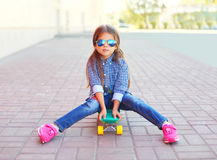 Fashion little girl child sitting on skateboard Royalty Free Stock Photo