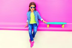Fashion little girl child sitting with skateboard in city on colorful pink wall. Background royalty free stock images