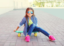 Fashion little girl child sitting on skateboard in city Stock Photography