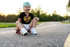 Fashion little girl child sitting on skateboard in city, wearing a sunglasses and t-shirt. Fashion little girl child sitting on skateboard in city, wearing a stock image