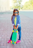 Fashion little girl child with skateboard wearing sunglasses and checkered hipster shirt Stock Photos