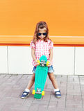 Fashion little girl child with skateboard wearing sunglasses and checkered shirt in city Stock Image