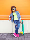 Fashion little girl child with skateboard wearing a sunglasses and checkered shirt over orange Stock Photography
