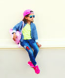 Fashion little girl child wearing a baseball cap and backpack. In the city on a white background Royalty Free Stock Images