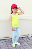 Fashion little girl child wearing a baseball red cap. In city Stock Photos