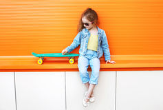 Fashion little girl child wearing a jeans clothes and sunglasses Royalty Free Stock Image