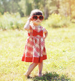 Fashion little girl child wearing red sunglasses outdoors Stock Image