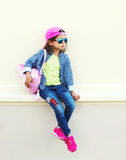 Fashion little girl child wearing a sunglasses, baseball cap and backpack in city over white. Background Stock Photography