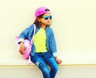 Fashion little girl child wearing sunglasses, baseball cap, backpack on city street on white. Background stock photos