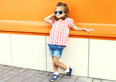 Fashion little girl child wearing sunglasses and checkered shirt over orange background in city Royalty Free Stock Image