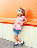 Fashion little girl child wearing sunglasses and checkered shirt standing in city Stock Photography