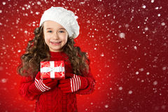 Fashion little girl with Christmas gift, on red background Royalty Free Stock Photography