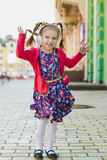 Fashion little girl with headphone listening music and dancing outdoor.  Royalty Free Stock Photo