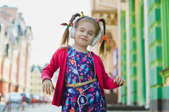 Fashion little girl with headphone listening music and dancing outdoor.  Stock Photography