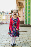 Fashion little girl with headphone listening music and dancing outdoor.  Royalty Free Stock Photos