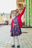 Fashion little girl with headphone listening music and dancing outdoor.  Royalty Free Stock Images
