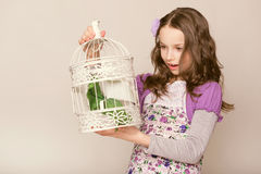 Fashion little girl looks on birdcage Royalty Free Stock Image