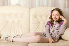 Fashion little girl lying on sofa Royalty Free Stock Photo