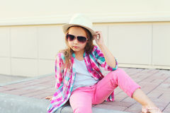 Fashion little girl model wearing a checkered pink shirt, hat and sunglasses Royalty Free Stock Photography