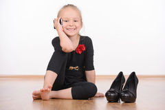 Fashion Little Girl. Portrait of a little fashion girl in a black dress and big shoes on a white background Stock Images
